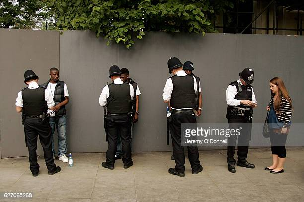 Police stop and search members of the public and assist another during Notting Hill Carnival on August 29 2011 in London United Kingdom
