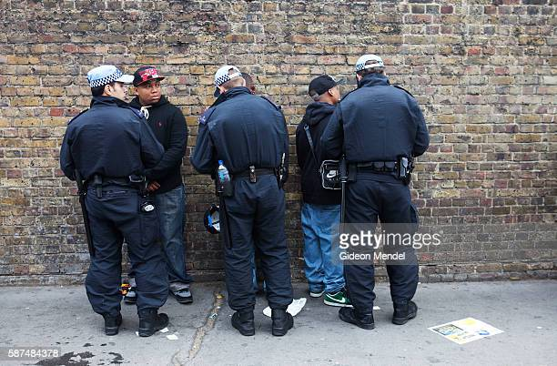 Police stop and search young black men at one of the entrances to the the Notting Hill Carnival For many victims of this experience it is a source of...