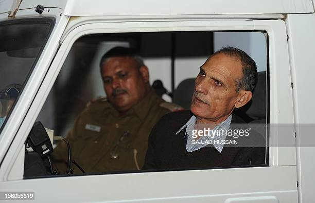 Police subinspector Baljit Singh Rana talks with police officers as he sits inside a police vechile outside his office in New Delhi on December 10...
