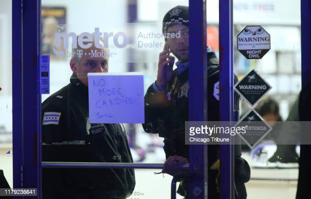 A police supervisor and officer stand inside a cellphone store in the 3700 block of West 26th Street in Chicago where a 7yearold girl who was shot...