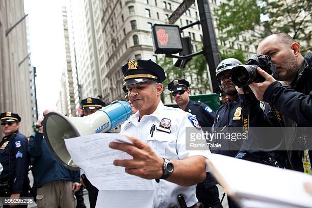 A police supervisor informs protestors on Wall Street that they are in violation of blocking pedestrian traffic during a demonstration in Lower...