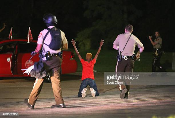 Police surround and detain two people in a car on August 13, 2014 in Ferguson, Missouri. Ferguson is experiencing its fourth day of unrest after...