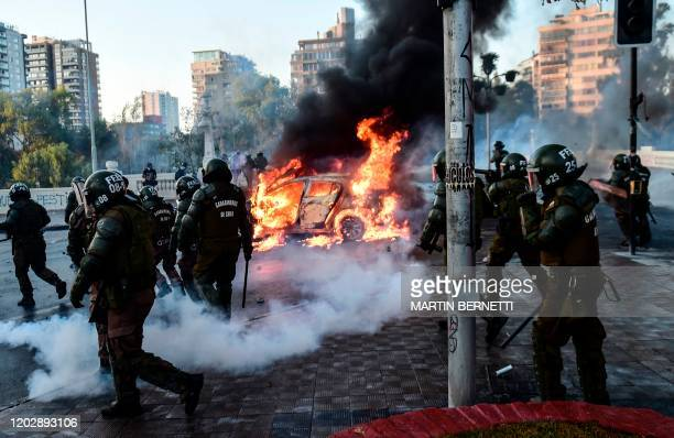 Police surround cars burning in flames outside the Hotel O'Higgins during a protest against Chilean President Sebastian Pinera's government in Vina...