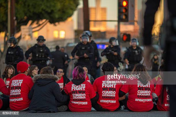 Police surround striking McDonald's restaurant employees sitting in an intersection after walking off the job to demand a $15 per hour wage and union...
