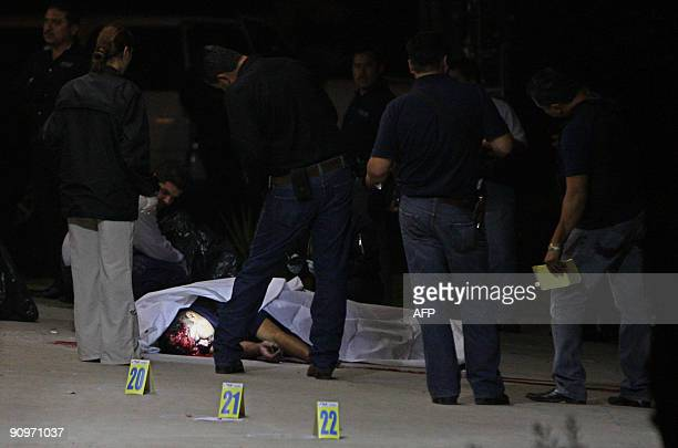 Police surround the corpse of a murdered colleague in Tijuana Mexico the night of September 18 2009 Three police officers were killed and one more...