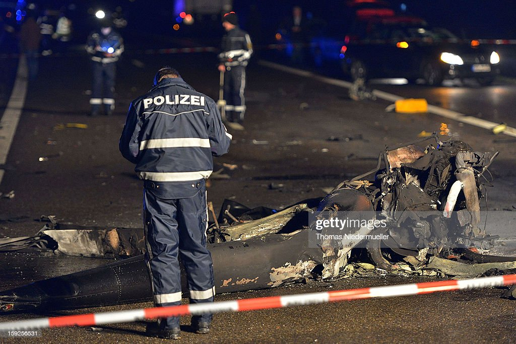 Police survey the wreckage of a helicopter that crashed onto the A6 highway on January 10, 2013 near Schwabisch Hall, Germany. According to police the helicopter struck a nearby power line and exploded, killing the pilot and leaving one vehicle driver with minor injuries.