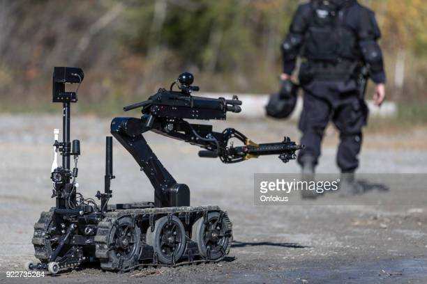 police swat officer using a mechanical arm bomb disposal robot unit - antiterrosimo foto e immagini stock