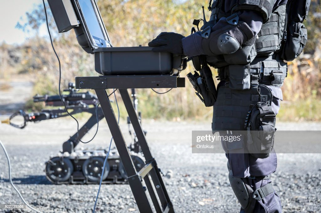 Police Swat Officer Using a Mechanical Arm Bomb Disposal Robot Unit : Stock Photo