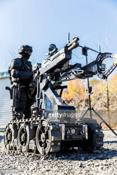 police swat officer using a mechanical arm bomb disposal robot unit - technology trade war stock pictures, royalty-free photos & images