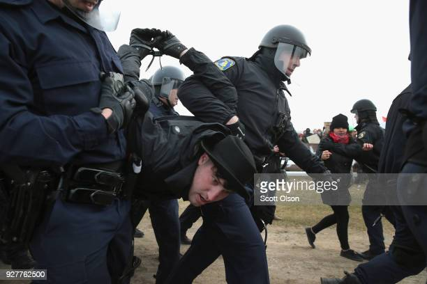 Police take a demonstrator into custody at Michigan State University before the start of a speech by white nationalist Richard Spencer on March 5...