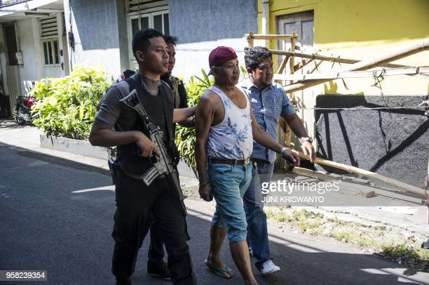 Police take a man in for questioning as they patrol around the Surabaya police headquarters following a suicide attack in Surabaya on May 14 2018 Two...