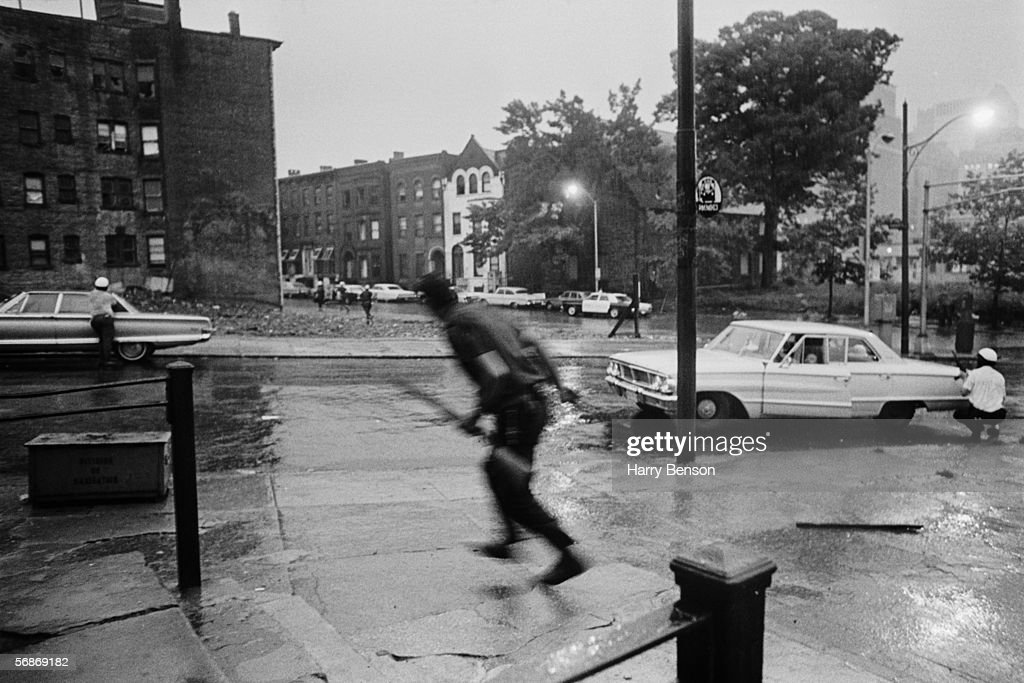 Police take cover behind parked cars during the riots in Newark, New Jersey, 14th July 1967. The disturbances began after a black taxi driver was arrested and beaten by police and lasted from the 12th to the 17th of July, resulting in 23 deaths.