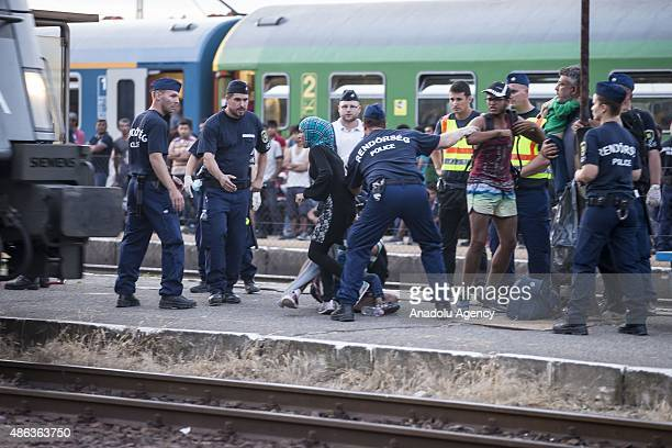Police take security measures as the migrants wait inside a train at the railway station in the town of Bicske Hungary September 3 2015 Migrants...