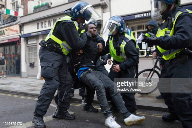 Police take some protesters as clashes break out between protesters supporting the Black Lives Matter movement and the opponents at Leicester Square...