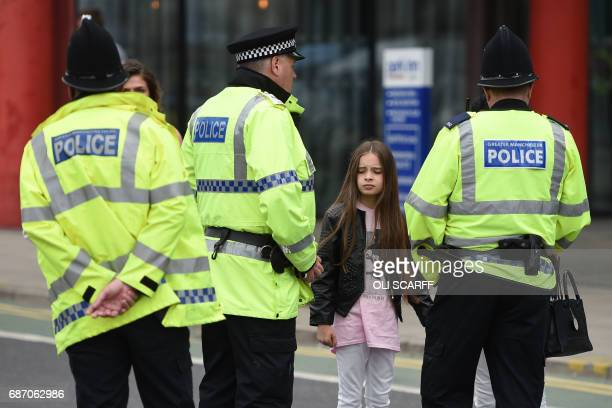 Police talk to people affected by the deadly terror attack at Manchester Arena in Manchester northwest England on May 23 2017 Twenty two people have...