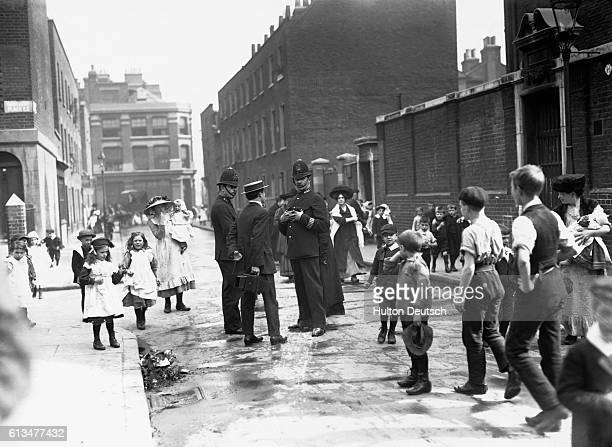 Police talk to the ringleader of a schoolboys' strike in London as he waits for scholars of the Bath Street High School to come out and join him.