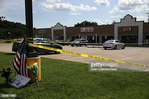 Police tape and a makeshift memorial frame the scene at an Armed Forces Career Center where earlier in the day an active shooter opened fire injuring...