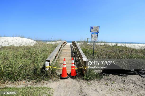 Police tape and pylons block the public access to Jacksonville Beach amid the coronavirus outbreak on March 21 2020 in Jacksonville Beach Florida...