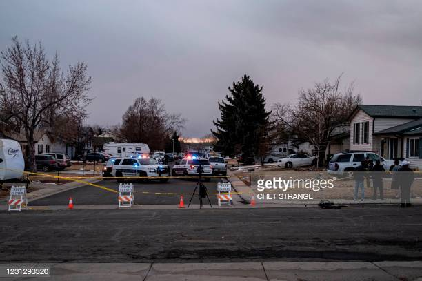 Police tape and road signs block a street where debris fallen from a United Airlines airplane's engine lay scattered through the neighborhood of...