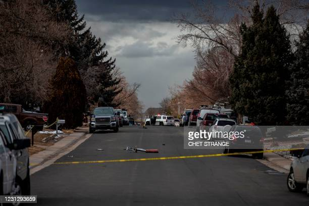 Police tape blocks a street where debris fallen from a United Airlines airplane's engine lay scattered through the neighborhood of Broomfield,...