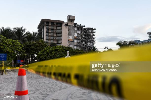 Police tape blocks access to a partially collapsed building in Surfside north of Miami Beach, on June 24, 2021. - A multi-story apartment block in...