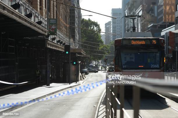 Police tape blocks off the street as police and emergency personnel work at the scene of where a car ran over pedestrians in Flinders Street in...