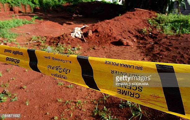 Police tape closes off part of a mass grave where the authorities found skeletal remains of over 150 people at the Matale hospital compound in...