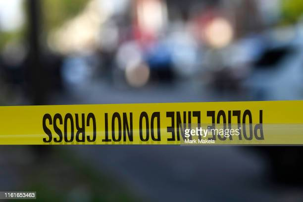 Police tape is stretched across a street near a residence during a shooting on August 14, 2019 in Philadelphia, Pennsylvania. At least six police...