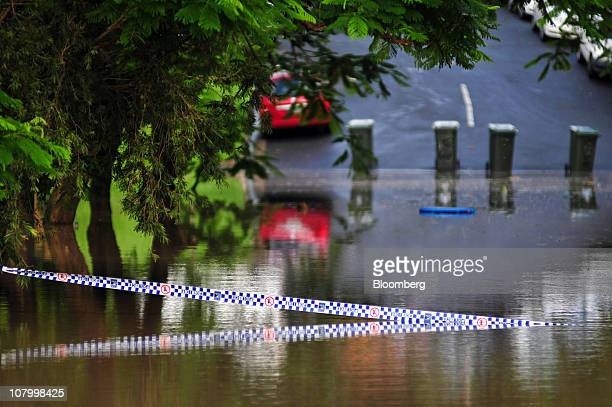 Police tape is submerged in flood waters on a street in Brisbane Australia on Wednesday Jan 12 2011 Floodwaters in Brisbane are rising after the...
