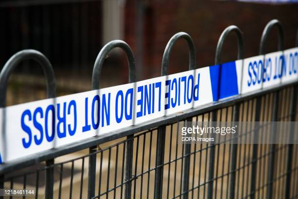 Police tape on a fence at a crime scene cordon in London.