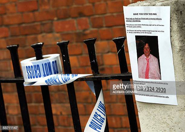 Police tape rests on a railing near a poster appealing for information about a missing person 08 July 2005 close to where a terrorist bomb exploded...