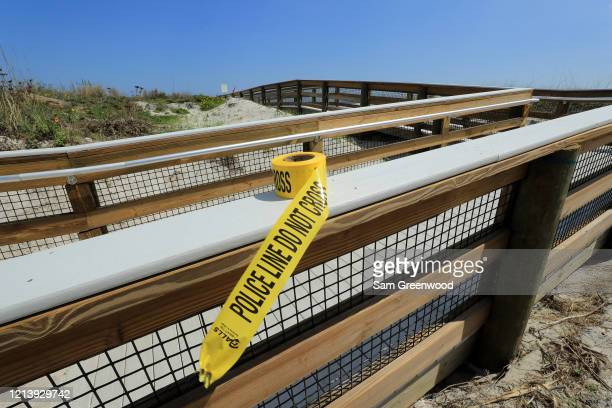 Police tape sits on a public access ramp at Jacksonville Beach amid the coronavirus outbreak on March 21 2020 in Jacksonville Beach Florida...