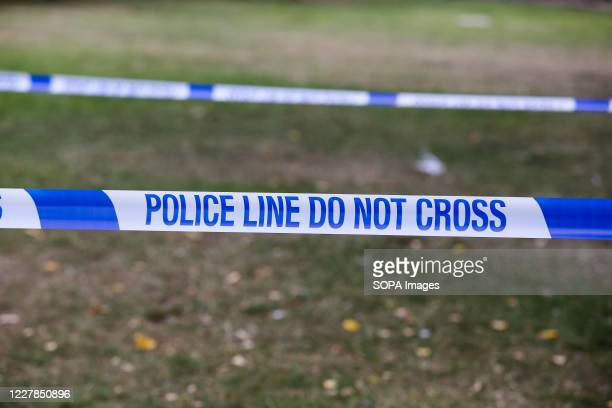 Police tape with 'Police Line Do Not Cross' written on it seen around a crime scene.