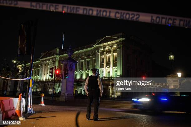 Police teams secure the roads behind a cordoned area following an apparent attack on two police officers at Buckingham Palace on August 25 2017 in...