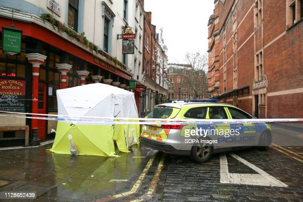 Police tent and a car are seen at the crime scene outside The Coach and Horses pub in Romilly Street in Soho. According to the police, a man aged 30...