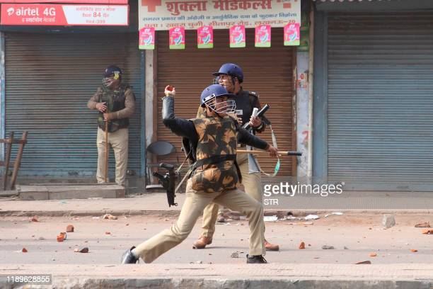 Police throw stones towards protesters during demonstrations against India's new citizenship law in Lucknow on December 19 2019 Indians defied bans...