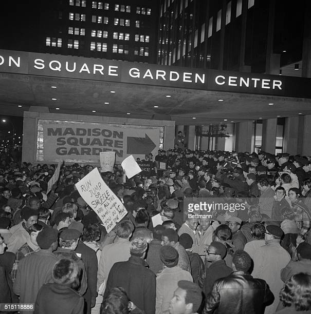 Police ticket holders demonstrators and newsmen mill about in front of Madison Square Garden prior to the centennial track meet sponsored by the...