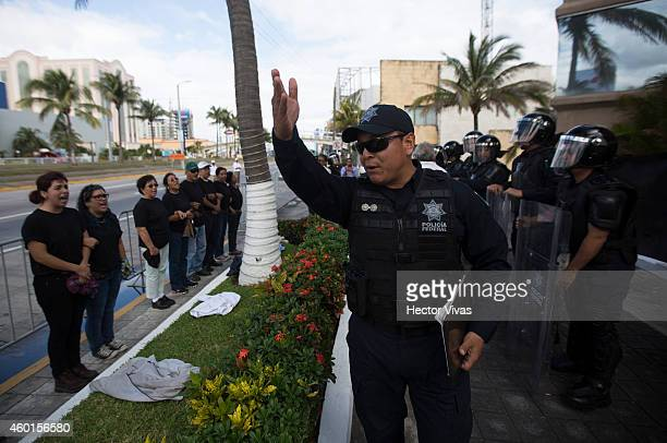 Police tries to stop the protesters who demonstrate against Mexican president Enrique Pena Nieto and his government to demand the appearance of 43...