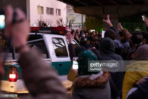 Police truck drives along an avenue as Iranians shout slogans during a gathering in front of a University to mark the memory of the victims of the...