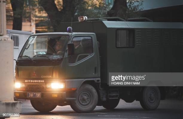 A police truck transporting defendants arrives at Hanoi People's Courthouse for the beginning of the trial of Trinh Xuan Thanh former oil tycoon who...