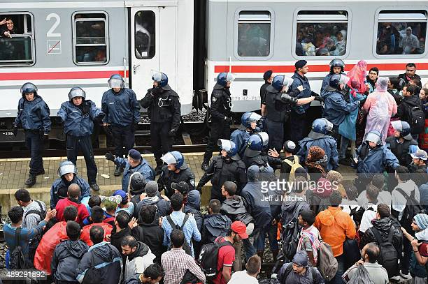 Police try and control migrants as they desperately try and board a train heading for Zagreb from Tovarnik station on September 20 2015 in...