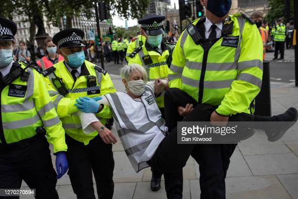 Police try to carry away an Extinction Rebellion protester who has 'gone floppy' at the point of arrest, which is reported to be something the...
