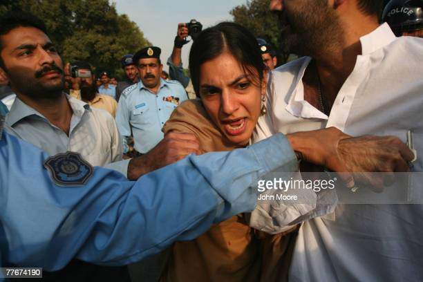 Police try to detain a demonstrator an an antigovernment protest on November 4 2007 in Islamabad Pakistan A small group of protesters held signs and...