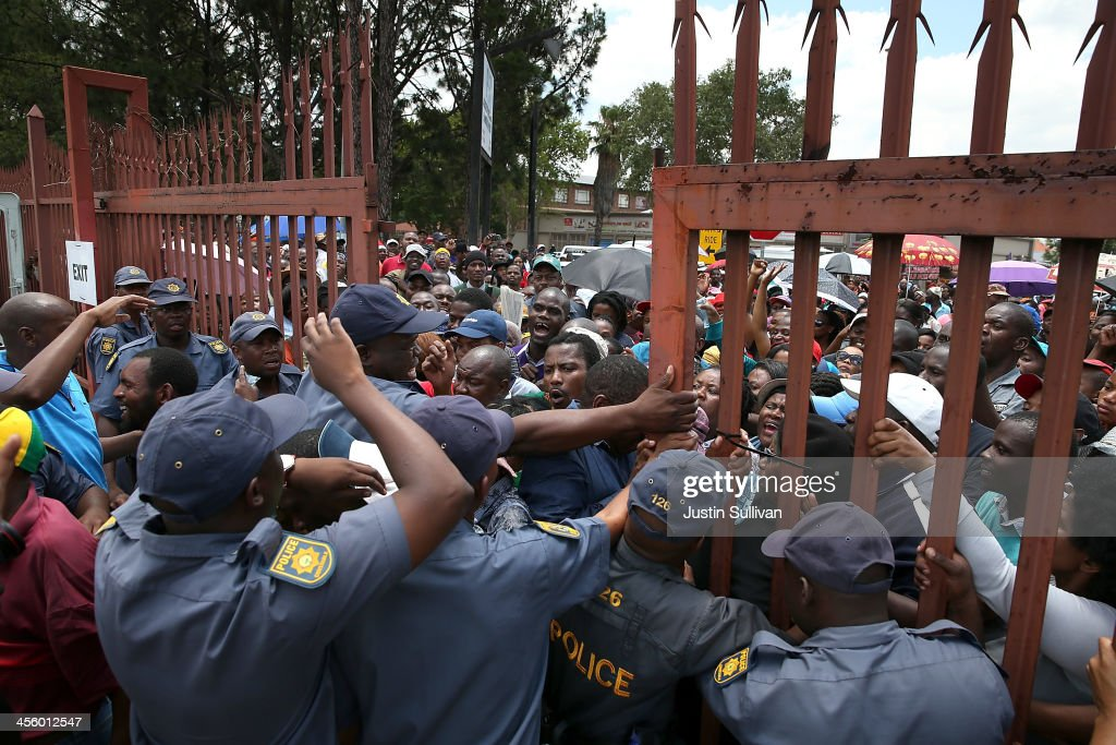 Police try to hold back people as they open a gate to a park and ride at the Tshwane Events Centre where buses were shuttling wellwishers to a line to view the body of former South African president Nelson Mandela as he lies in state at the Union Buildings on December 13, 2013 in Pretoria, South Africa. Nelson Mandela's body will lie in state for three days as part of a week of events commemorating the life of former South African President. Mr Mandela passed away on the evening of December 5, 2013 at his home in Houghton at the age of 95. Mandela became South Africa's first black president in 1994 after spending 27 years in jail for his activism against apartheid in a racially-divided South Africa.