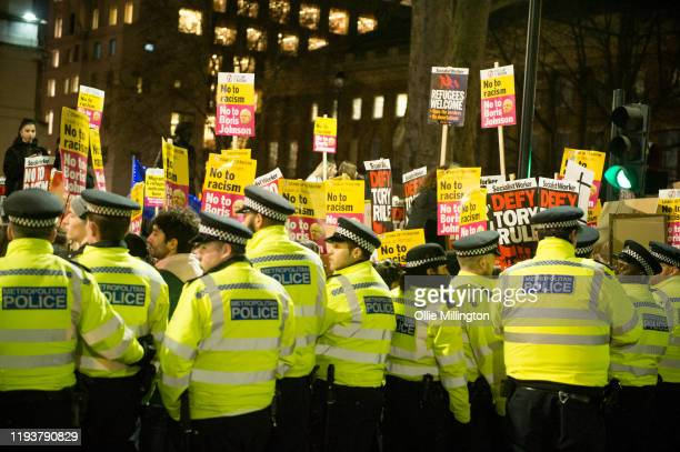 Police try to keep the road open for traffic as Stand Up to Racism hold a protest outside Downing Street called Not My Prime Minister on December 13...