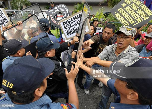 Police try to push away Filipino protesters burning a mock US flag outside the American embassy in Manila, on March 4, 2008. The protesters, who are...