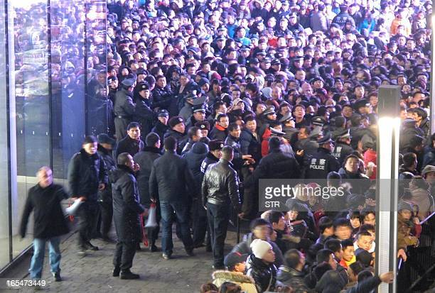 Police try to seal off the area as thousands of customers queue up outside an Apple store in Beijing's upmarket Sanlitun shopping district in Beijing...