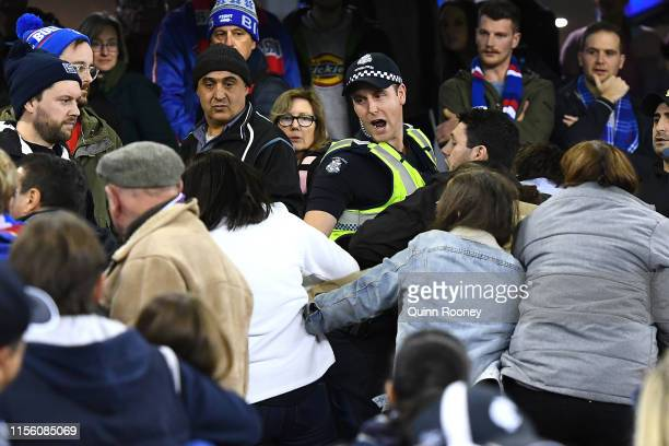 Police try to seperate a fight in the crowd during the round 13 AFL match between the Carlton Blues and the Western Bulldogs at Marvel Stadium on...