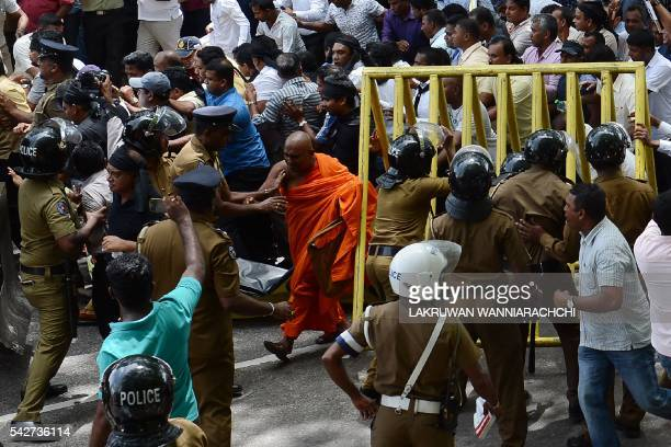 TOPSHOT Police try to stop demonstrators from marching towards the Central Bank of Sri Lanka building in Colombo on June 24 2016 Protestors demand...