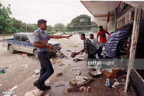 Police try to stop looters at Taurama shopping centre after a demonstration at Murray Army Barracks got out of hand and the demonstrators broke into...